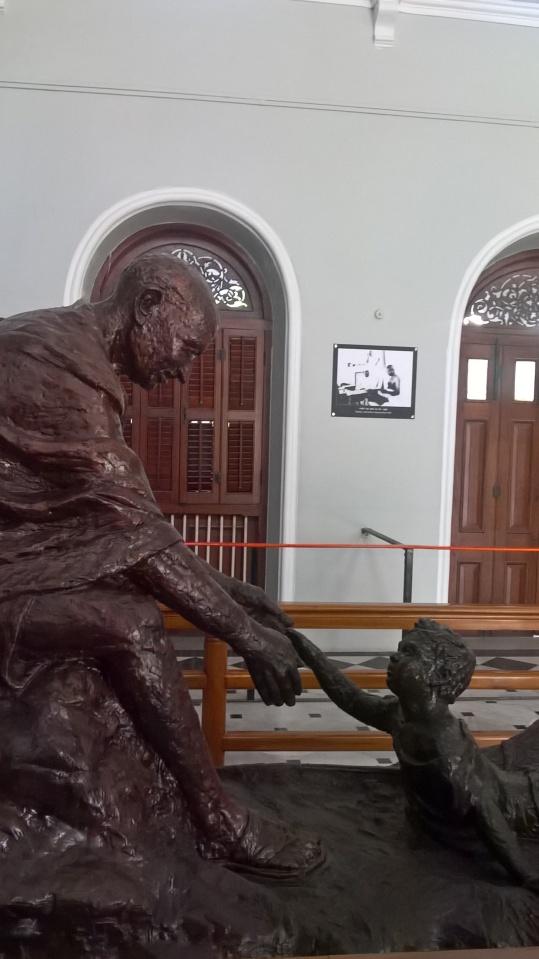 gandhi helping child sculpture